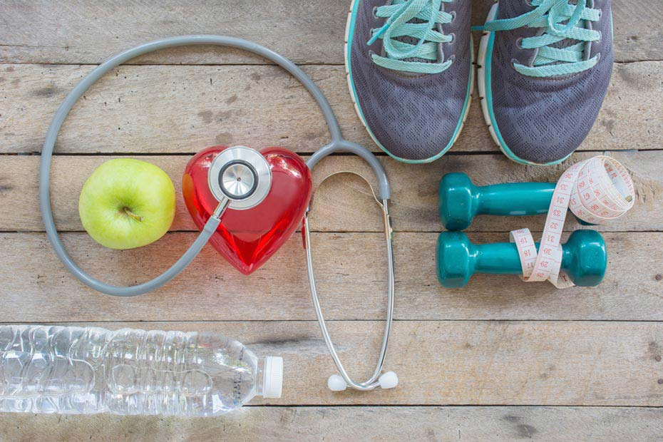 sports equipment, water and an apple, signifiying nutrition and exercise for a healthy heart