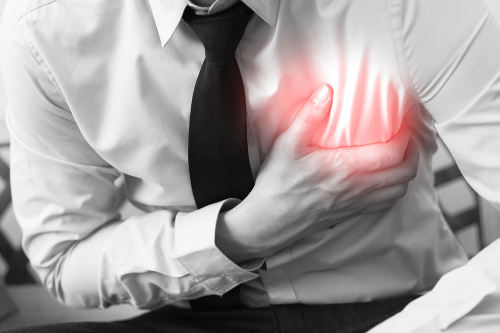 man clutching chest in pain during heart attack